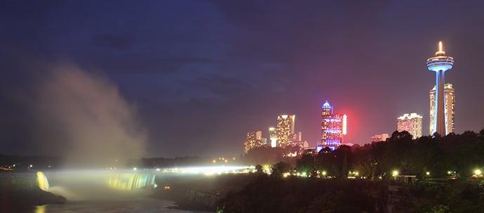 Niagara Falls at night with lights at Skylon and surrounding buildings.